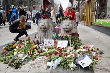 STOCKHOLM 2017-04-08 Människor lägger ned blommor och ljus vid två sk Stockholmslejon i betong på Drottninggatan i centrala Stockholm. En kapad lastbil körde på ett stort antal personer på Drottninggatan vid 15-tiden på fredagen. Fyra personer dödades och 15 skadades. Polisen utreder händelsen som ett misstänkt terrordåd. Foto: Jonas Ekströmer / TT / Kod 10030